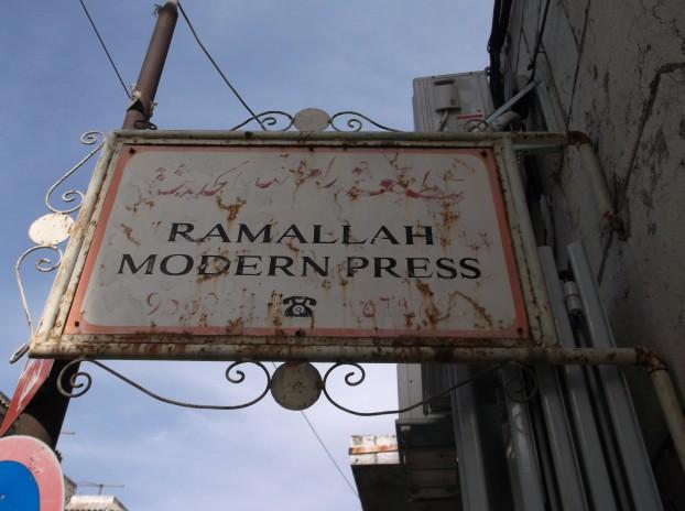 Uithangbord in het centrum van Ramallah. Hier zat vroeger een kantoor van een krant of tv station. Nu een kledingmaker, maar het bord is nooit weggehaald.. Foto Lisanne Oldekamp