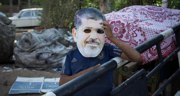 Een kind draagt een masker met het gezicht van de afgezette Egyptische president Morsi. Foto Ester Meerman