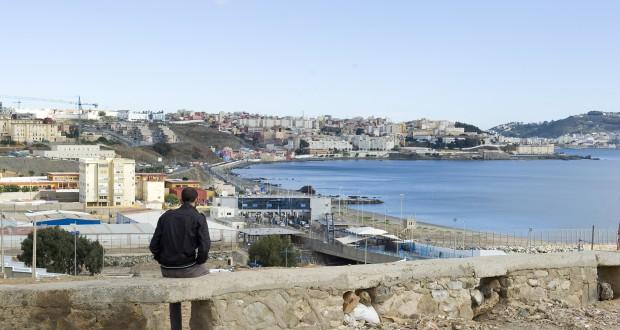 Een man kijkt vanaf Marokkaans grondgebied uit over de Spaanse enclave Ceuta. Foto Rik Goverde